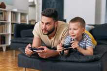 Father Playing Video Games With His Son. They Are Sitting In Living Room