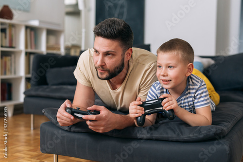 Fototapeta father playing video games with his son