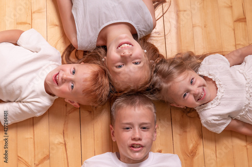 Tela children lie on the floor and looking at camera