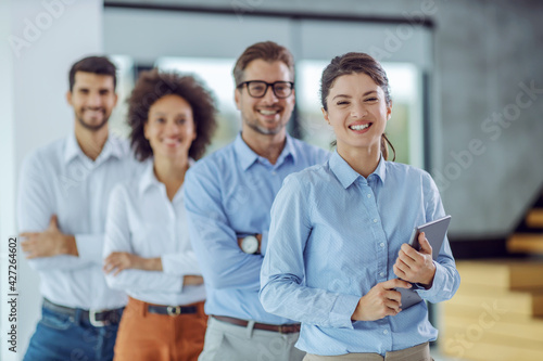 Fotografia, Obraz Multicultural group of business people standing with arms crossed in a row in office