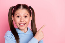 Photo Portrait Of Small Schoolgirl Pointing Finger Blank Space Smiling Isolated On Pastel Pink Color Background
