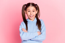 Photo Portrait Of Funny Schoolgirl Smiling With Crossed Hands Wearing Blue Clothes Isolated On Pastel Pink Color Background