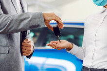 Close Up Of Car Seller Handing Car Keys To A Customer.