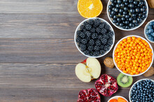 Mix Of Fresh Berries, Nuts And Fruits. Healthy Food Contains A Lot Of Vitamins And Useful Trace Elements.Brown Wooden Background. Copy Space.