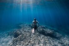 Male Freediver Glides Underwater In Blue Sea