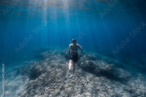Fényképezés Male freediver glides underwater in blue sea
