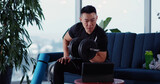 Young Chinese Sportsman Stays Home Works Out with Dumbbells Lifting Weights Practicing with Video Tutorial Laptop. Bodybuilding. Active Lifetstyle.