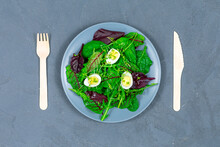 Lunch Bowl Of Lettuce Leaves With Eggs With Wooden Fork And Spoon On Gray Background. Healthy Food Concept. PP. View From Above. Zero Waste.