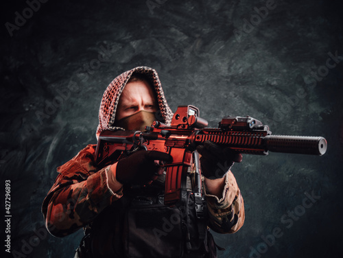 Obraz na plátně Armed soldier with hood and modern equipment aims a rifle