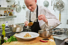 Chef Without Hair Prepares Scampi In The Kitchen. He Holds A Pot In His Hand And Has A Spoon In His Hand. In The Foreground You Can See Chily, Pepper, Salt, Parsley. Feel Like Going Out For Dinner?