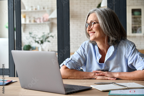 Fototapeta Senior adult mid 50s age watching at window at home sitting at table with laptop. Feeling happy and smiling to thoughts about future positive vision of successful training career after learning. obraz