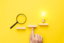Abstract Business Strategy Concept. Steps To Idea Symbol Shown As Light Bulb Over Yellow Background. Inspiration And Innovation Conceptual