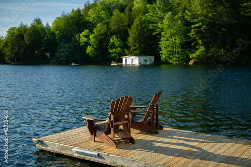 Billede på lærred Two Adirondack chairs on a wooden dock facing a lake in Muskoka, Ontario Canada during a sunny summer morning