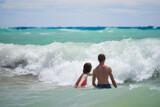 Fototapeta Fototapety z morzem do Twojej sypialni - Młodzież aktywnie wypoczywająca w słoneczny letni dzień  nad ciepłym morzem, kąpiele morskie wśród fal.