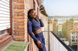 black afro woman dressed in sportswear listening to music on headphones very happy on the balcony of her house because she is going to start exercising at home due to the covid19 coronavirus pandemic