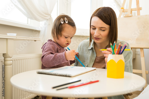 Kid with down syndrome drawing with pencil on paper while sitting at the table