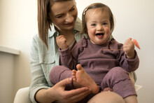 Girl With Down Syndrome Sitting At The Laps Of Her Mother