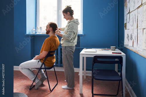 Man having haircut at home by his woman during coronavirus covid-19 pandemic Wallpaper Mural