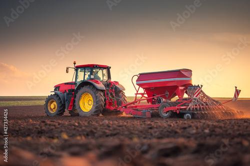 Obraz na plátně Farmer with tractor seeding crops at field