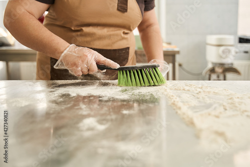 Obraz na plátne Female baker wearing protective gloves cleaning with brush table of the flour