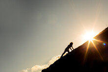 Man Climbing A Mountain With The Sun In The Background. Concept Of Never Give Up On Your Goals And Dreams