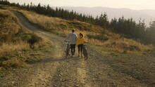 Guy And Girl Having Walk With Bicycles. Bicyclists Looking Around Landscape