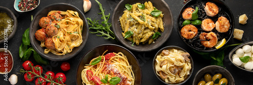 Foto Assortment of Italian pasta with traditional sauces for dinner on dark background