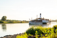Large Retro Tourist Steamer With A Pipe Is Full Of People And Sails Along The Calm Elbe River Next To A Green Wild Coast On A Sunny Day At Sunset In The City Of Dresden. Travel Concept