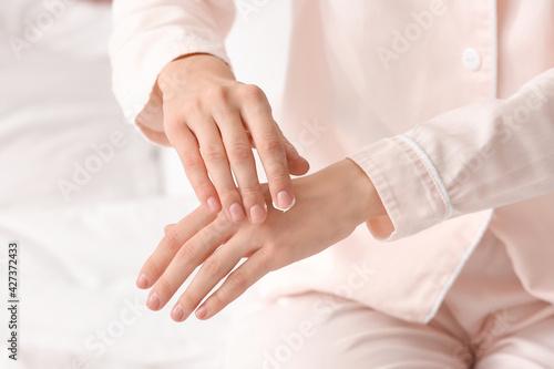 Slika na platnu Young woman applying cream on her hands, closeup