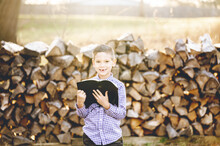 Little Boy Reading The Holy Bible While Standing In Front Of Stacked Firewood In A Field