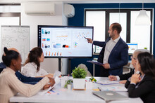 Manager Holding Briefing Presentation In Conference Room Monitor Project. Corporate Staff Discussing New Business Application With Colleagues Looking At Screen
