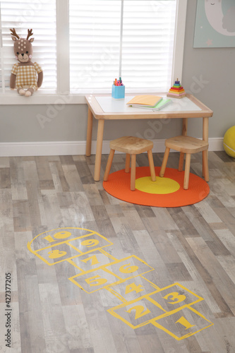 Yellow hopscotch floor sticker in room at home