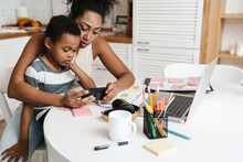Black Mother And Son Using Mobile Phone While Sitting Together At Home
