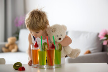 Cute Toddler Child, Blond Boy, Drinking Freshly Made Fruit Juice At Home