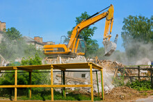 An Excavator Destroys An Old Building On A Summer Day