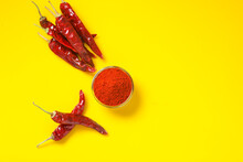 Dry Red Chilli With Chilli Powder In Glass Bowl On Yellow Background.