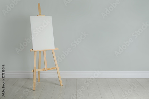 Valokuva Wooden easel with blank canvas near light wall. Space for text