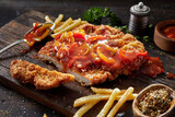Appetizing schnitzel with pepper sauce and fries