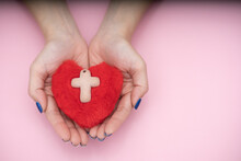 A Red Heart With The White Cross Inside Is Resting In The Palm Of Hands
