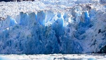 Hubbard Glacier Wall. Located In Eastern Alaska Near Juneau Showing The Amazing Blue Colours As Pieces Of The Ice Falls.
