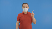 Young Man Wearing A Medical Mask Protecting From The Epidemic. With His Finger, He Points To His Mask, Then The Ad Space Above It.Indoor Studio Shot Isolated On Blue Background.