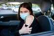 Portrait of a young woman in car shows arm with patch, smiling after having the vaccine against Coronavirus Covid-19 immunizing in the forecourt of the hospital - Person bares shoulder after injection