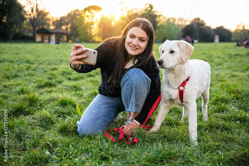 Young woman at the park at sunset takes a smartphone selfie together with her fa Fototapet