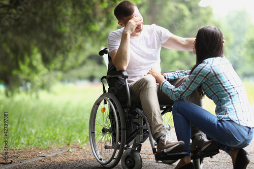 Foto Disabled man in wheelchair communicates with woman in park