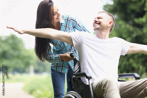 Happy man in wheelchair for walk with woman Fototapete