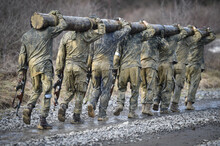 Special Forces Military Training Carrying A Big Log. Photograph Detail With Military Equipment And Assault Rifle.