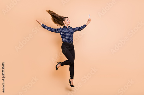 Obraz Full length profile side photo of young woman happy smile jump up make selfie cellphone isolated over beige color background - fototapety do salonu