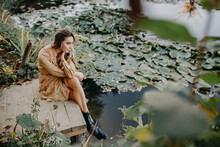 Young Woman Wearing A Maxi Chiffon Dress Sitting On A Wooden Pier By A Pond With Water Lilies.