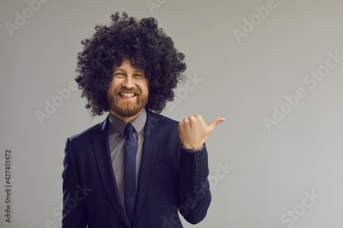 Funky bearded business man in black curly afro style hair wig pointing with thumbs up at grey right copy space aside Fototapeta