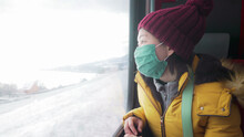 Travel During Covid19 - Young Happy And Beautiful Asian Chinese Woman In Face Mask Looking To Snow Through Train Window Traveling During Winter Holiday